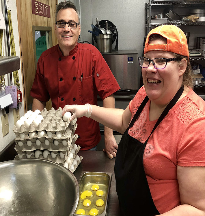 Chef Philip and Liz stand with eggs in the kitchen.