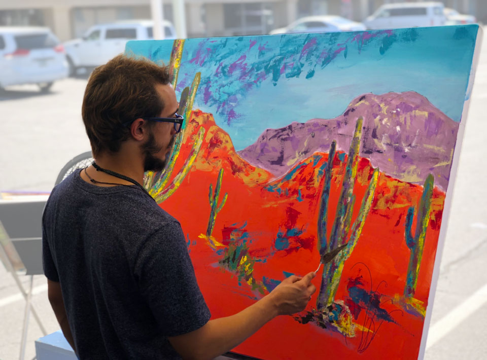 An artist painting a colorful desert scene