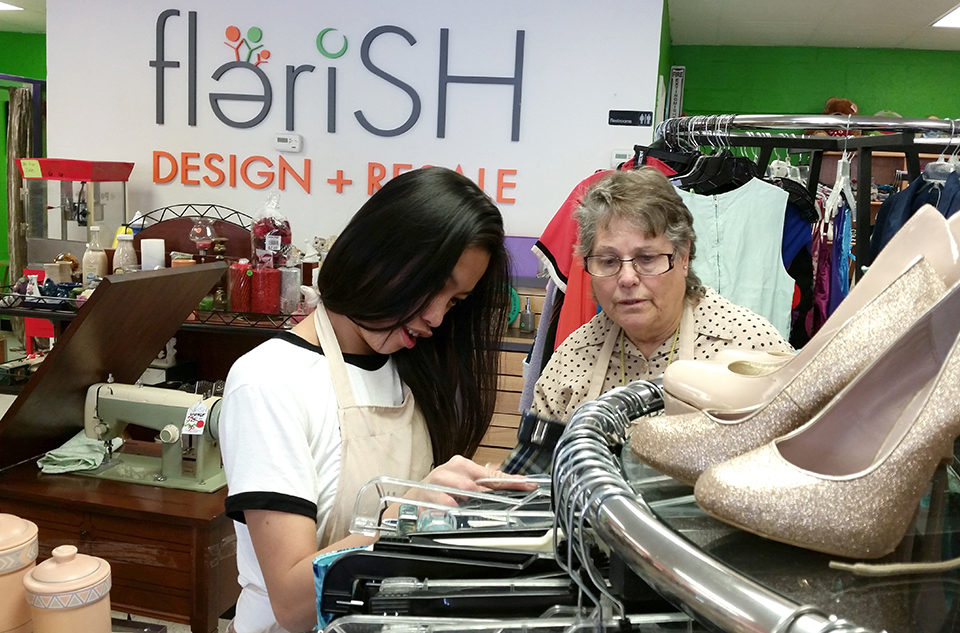 Two friends look at clothing on hangers at the Flerish store.