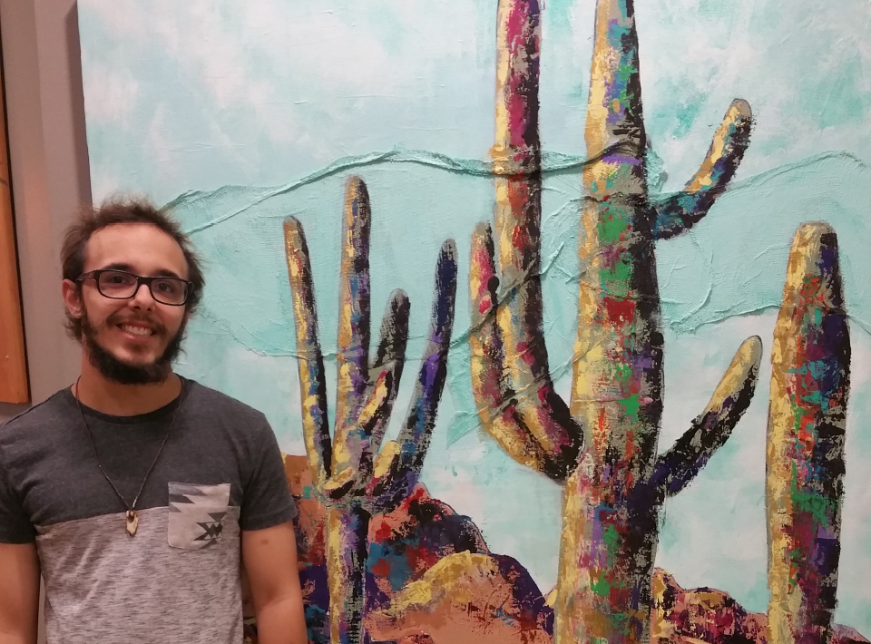 A young man stand beside a painting of cacti