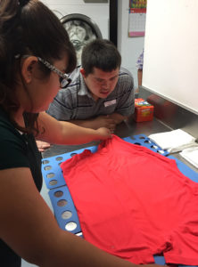 Teens learning skill folding shirts