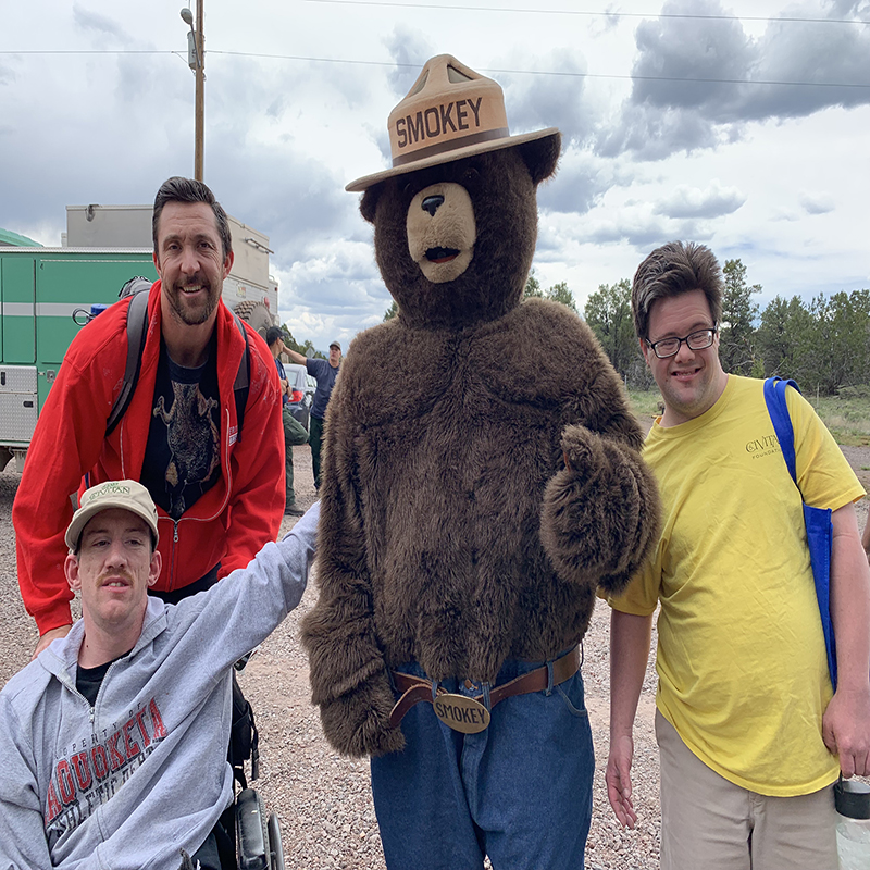 Smokey the Bear takes photo with several campers.