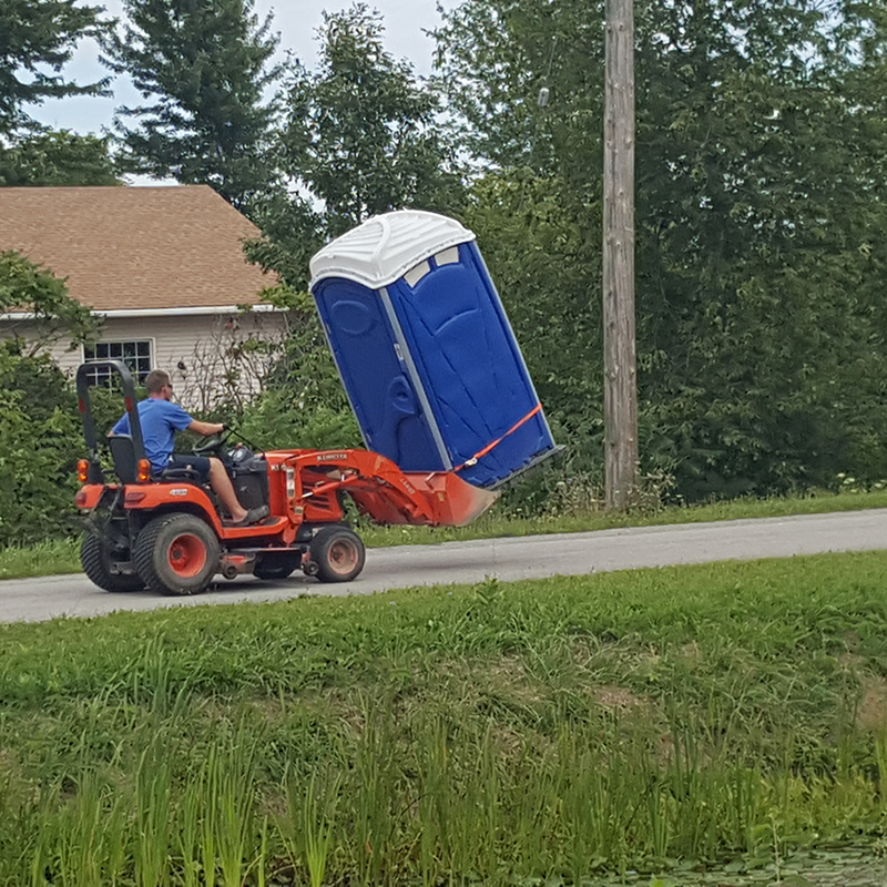 Funny picture of Porta John being carried by tractor