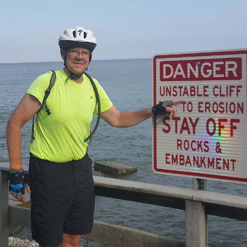 Frank Nightingale standing next to sign telling visitors to watch out for unstable cliff.