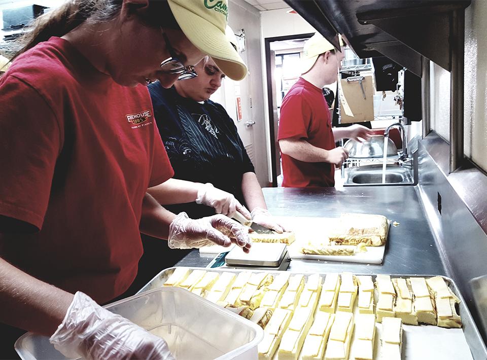 Members working in the kitchen preparing burritos