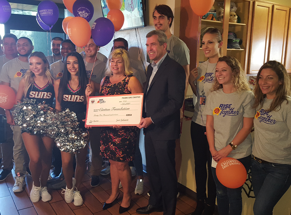 Civitan CEO Dawn Trapp accepts a check from the Phoenix Suns